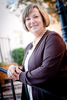 Eileen Kugler leaning on railing for business portrait in downtown alexandria va