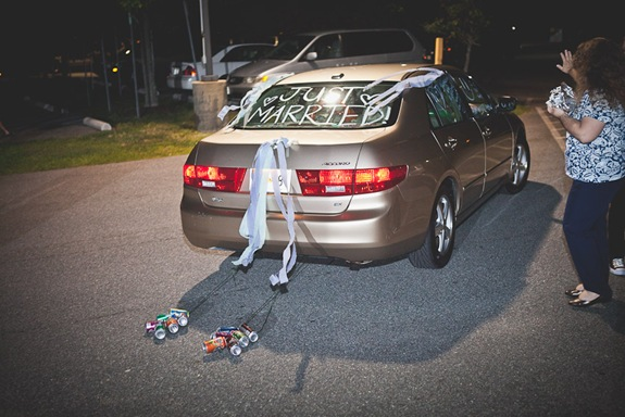 bride and groom drive away after wedding