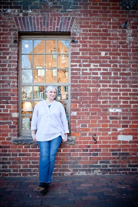 woman leaning up against window in old town alexandria