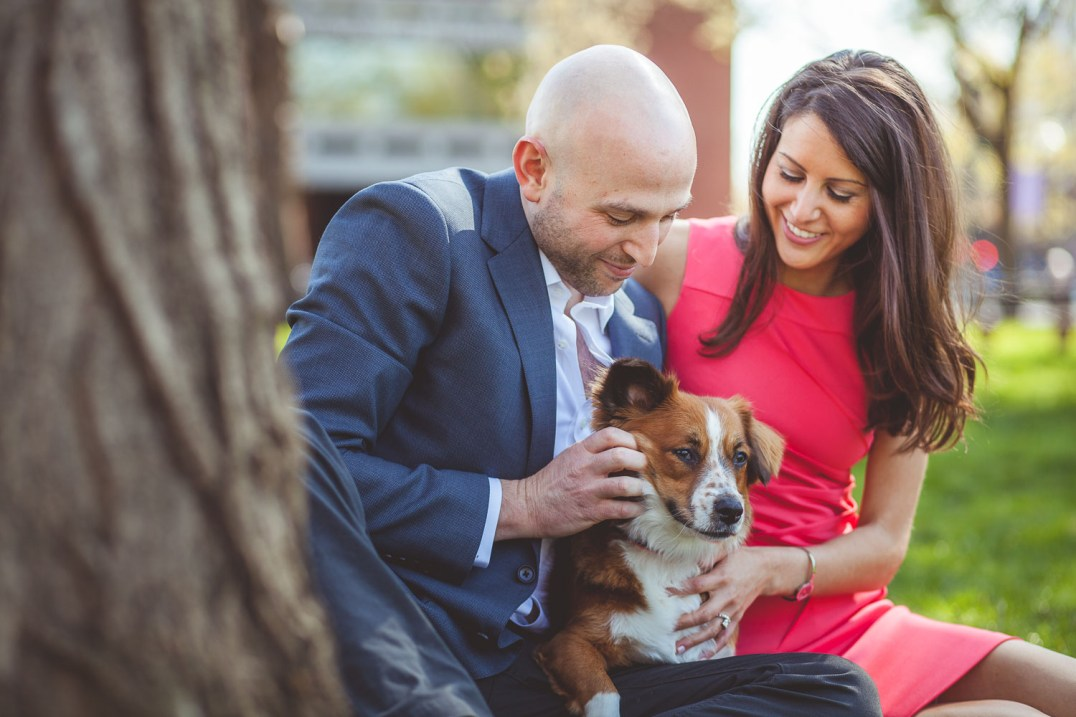 engaged couple playing with their dog.