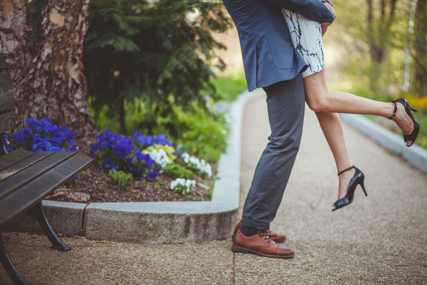 Photo of engaged couple's feet as man lift's his fiancee off the ground.