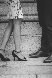 black and white photo of engaged couple's feet as they share a romantic moment.
