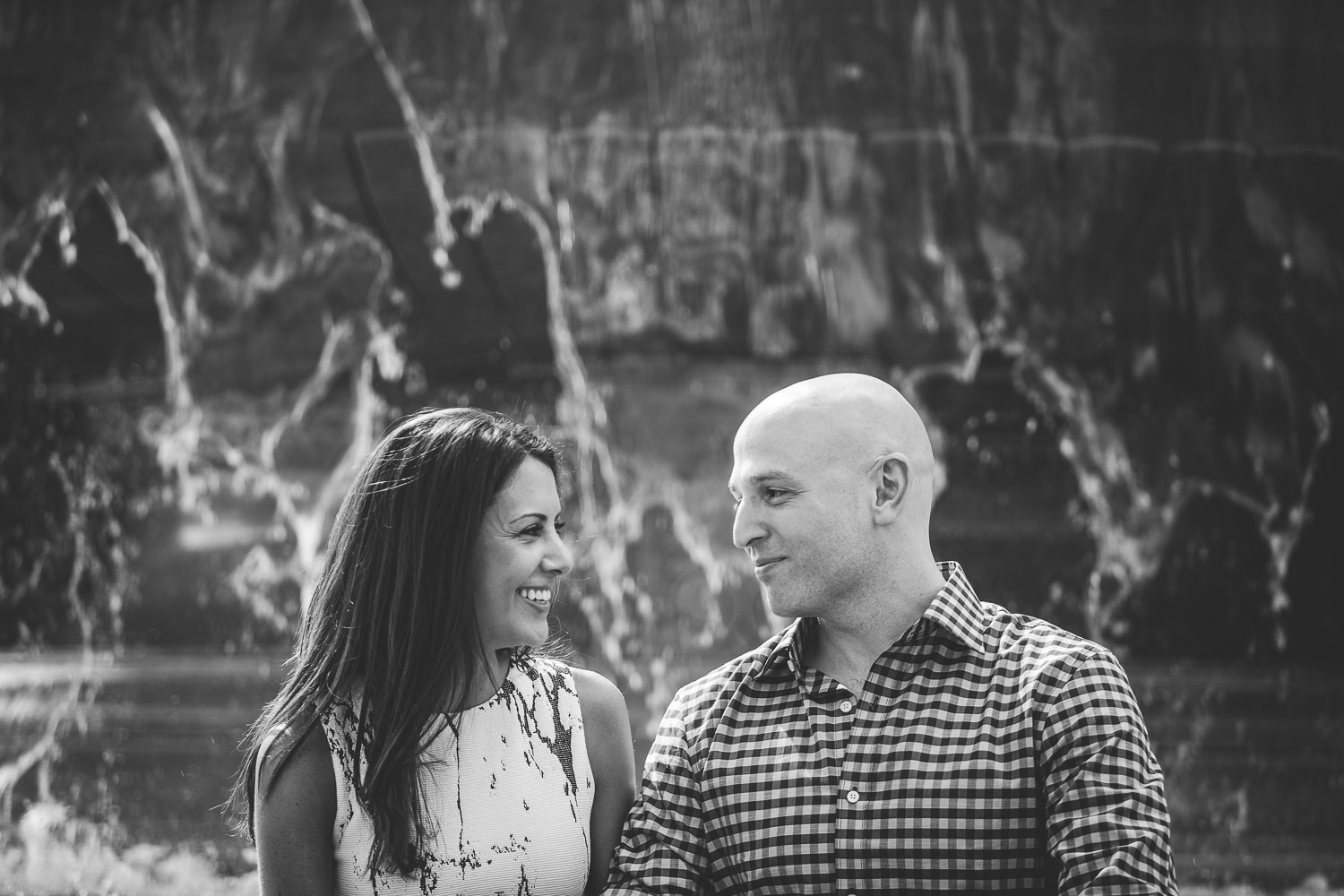 Black and white photo of an Engaged couple in front of a fountain in DC.