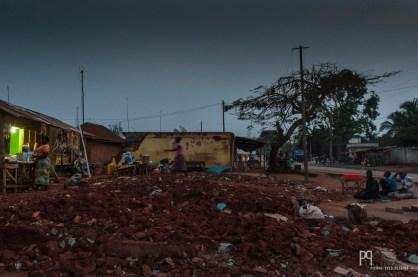 Le soleil tombe sur un groupe d'hommes priant le long de la voie. Allada est en ruine: les pelleteuses chinoises ne se sont pas posées de question, la route passera là où le gouvernement l'a décidé. // Allada - 2014
