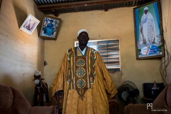 Le roi de Banikoara incarne, comme les autres rois du Bénin, une autorité morale séculaire respectée politiquement. A l'issu de ma première visite, il pose fièrement devant des portraits de ses ancêtres. // Banikoara - 2016