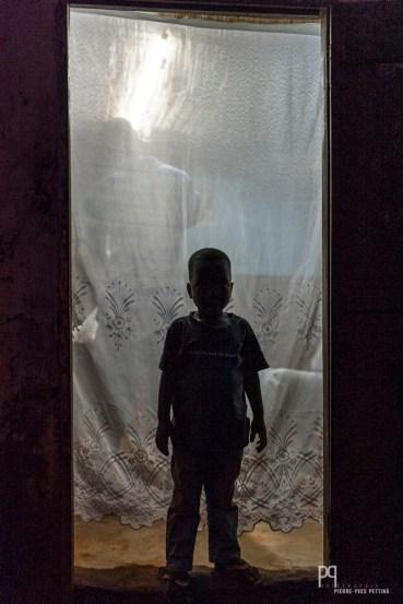 Planté sur le pas de porte du coiffeur, ce petit garçon attend sagement que son père ait terminé. // Allada - 2014