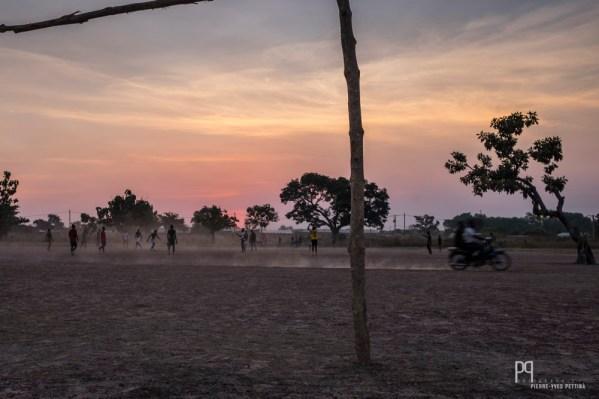 Les terrains n'étant pas clairement définis, il est courant de voir des motos ou des animaux zigzaguer entre les joueurs. // Banikoara - 2017