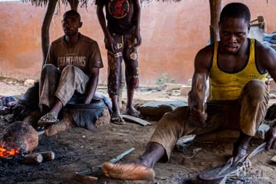 Dans le quartier des forgerons, les artisans s'activent du matin au soir. Ventilé à la main (à gauche), le four porte le charbon à incandescence et permet de travailler le fer. Sous le couvert de branches sèches où règne une chaleur insoutenable, les forgerons martèlent sans relâche pour réaliser des outils agricoles qui seront vendus sur le marché voisin. // Kérou - 2019