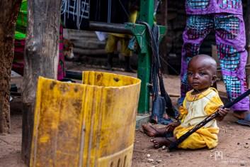 Petite fille jouant sous le métier à tisser de sa maman. Réputées pour leurs étoffes bariba, les tisserandes du nord Bénin produisent des pièces, en coton, réalisées sur des métiers verticaux ou horizontaux. Aux coloris sobres et aux motifs géométriques, les pagnes sont portés tous les jours et très demandés lors les grandes occasions, comme la fête de la Gani, à Nikki.