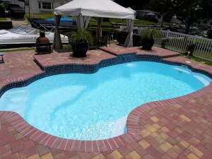 Millennium 12' x 25' Pettit Fiberglass Pool w/raised waterfall feature and paver deck