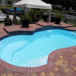 Millennium 12' x 25' Pettit Fiberglass Pool w/raised waterfall feature and paver deck