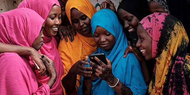 Young Somali women look at a smartphone at Dadaab refugee complex, in northeast Kenya, on April 16. (Yasuyoshi Chiba/AFP/Getty Images)
