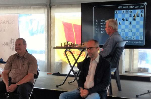 John van der Wiel en Erik van den Doel zitten met hun rug naar het scherm en spelen op die manier hun onderlinge partij.