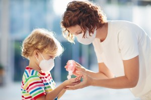 child and mother wearing mask and using hand sanitizer