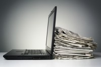 Photo of a laptop next to newspapers.