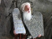 Mel Brooks holding the three tablets with 15 Commandments, dressed as Moses.