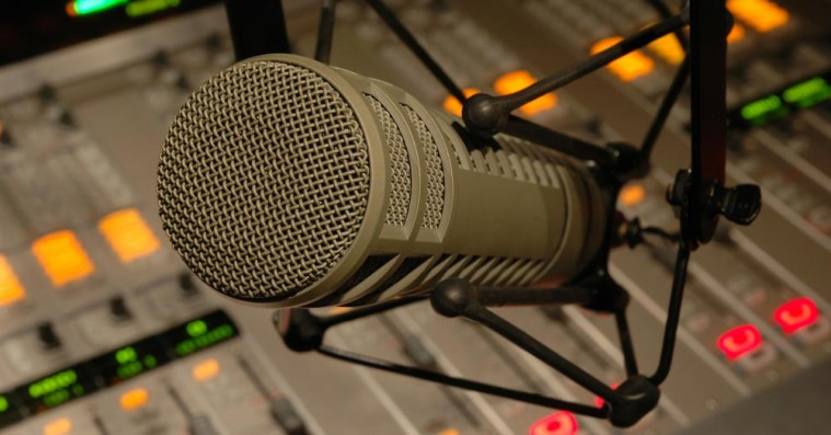 Image of a radio microphone in front of the radio studio mixing board.