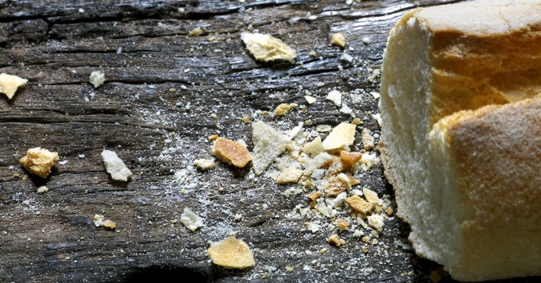 Breadcrumbs on a wooden table, beside a French baguette (French bread).