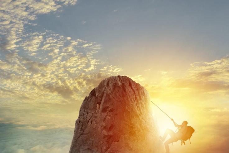 homme qui grimpe une montagne