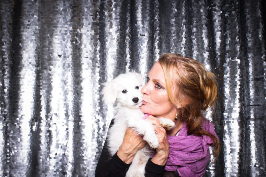 A lady in a pink scarf kissing her adorable pup in the culver city photo booth