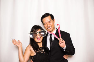 A couple wearing props and laughing in the photo booth