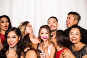 Friends kissing the bride and groom in the photo booth