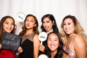 Girlfriends posing with Team Bride signs in the photo booth