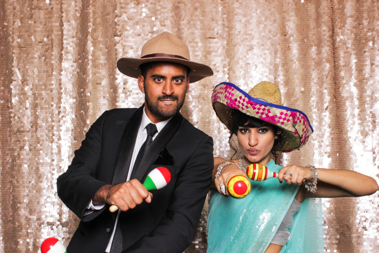 A girl and a guy posing in big hats with maracas in the pasadena photo booth