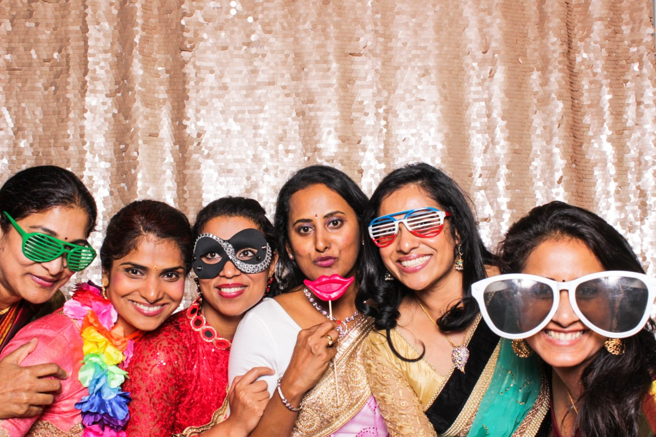 A group of girlfriends wearing colorful glasses and props in the pasadena photo booth