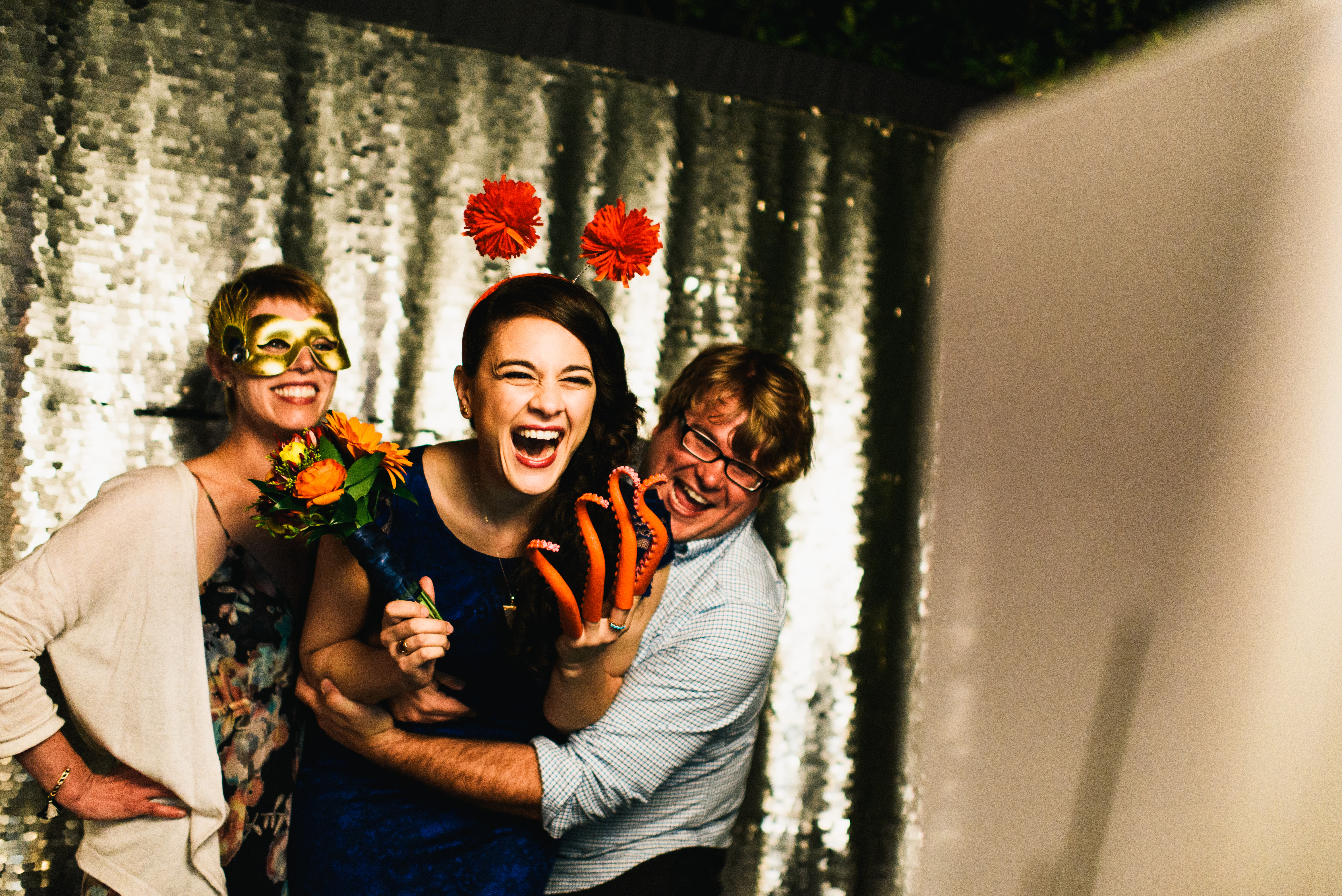 A bridesmaid laughing with friends in front of the Phizpix photo booth rental