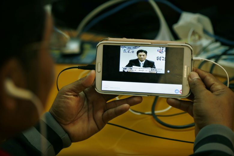 A person watches a live telecast of the 2017 national commune elections result on his smartphone yesterday in Phnom Penh.