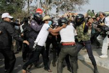 A man is beaten by authorities during a clash that erupted last week after protesters were blocked from Phnom Penh's Freedom Park
