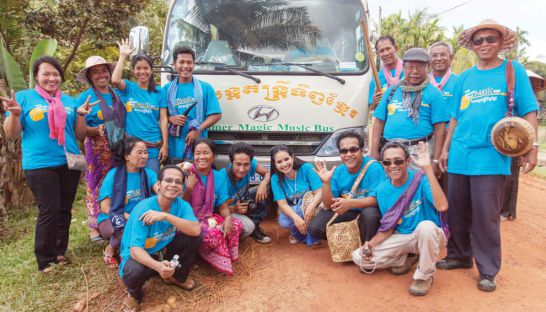 Both inside and outside the vehicle, the Khmer Magic Music Bus musicians spend the journey singing, laughing and clapping.
