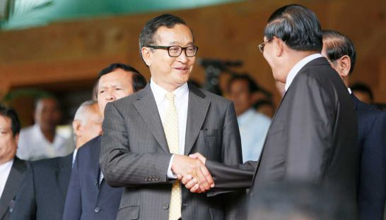 Opposition leader Sam Rainsy shakes hands with Prime Minister Hun Sen after a meeting at the Senate building