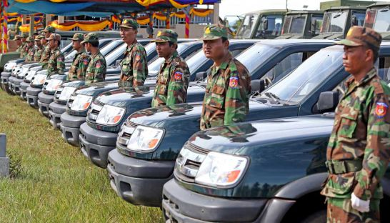 Military personnel stand next to newly donated vehicles