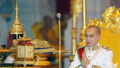 Cambodia's King Norodom Sihamoni sits on his throne beside his crown and sword during his coronation ceremony at the Royal Palace in Phnom Penh on October 29, 2004