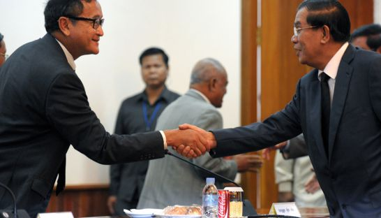 Prime Minister Hun Sen (right) shakes hands with opposition leader Sam Rainsy during a meeting at the National Assembly in Phnom Penh in 2013. Tang Chhin Sothy