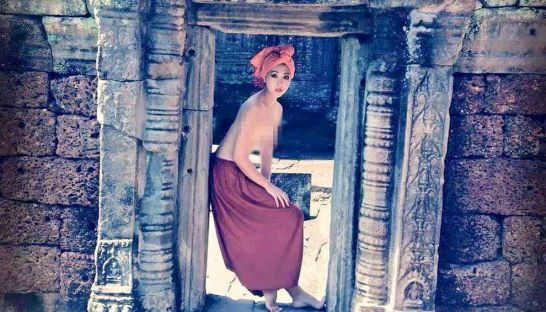 A topless woman poses for a photo at the temple of Banteay Kdei
