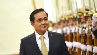 Thai Prime Minister Prayuth Chan-ocha walks past an honour guard in Beijing