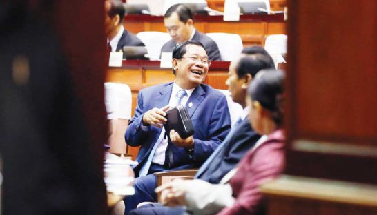 Prime Minister Hun Sen is seen through a door at a National Assembly session yesterday where controversial changes to the Law on Political Parties were approved.