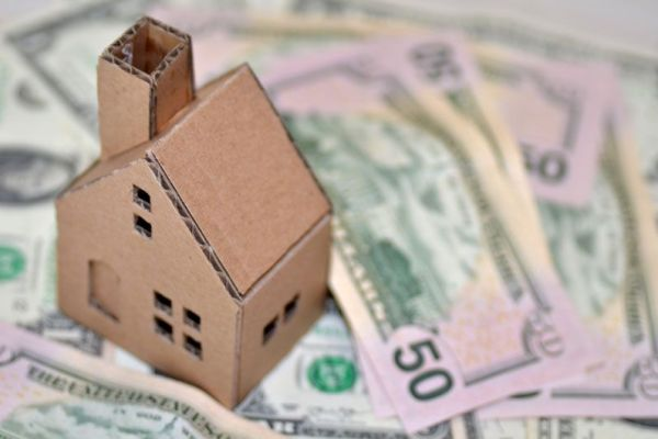 cardboard home on top of cash