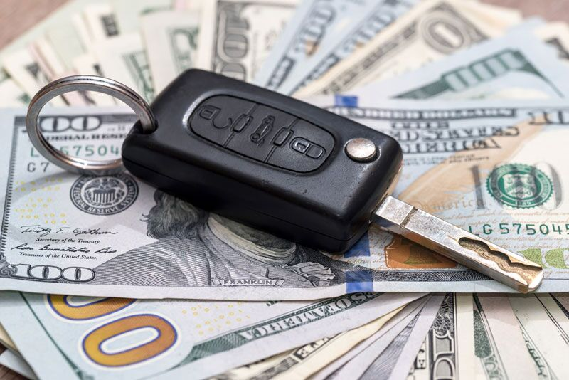 car key on top of cash