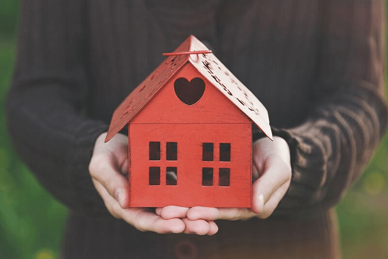 red toy home in hands