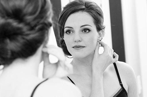 Woman Wearing Earring in Mirror