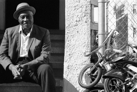 Life – A man with a good face and gentle hands sits on his stoop beside childrens' bikes.