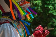 Life – colorful costumed Peruvian performer in ribbon headdress dances with scissors