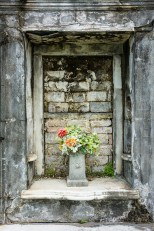 Conceptual – vase of plastic flowers in alcove of crypt