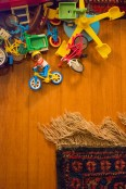 Conceptual – A Playmobil figure on a bicycle appears to escape a pile of plastic toys