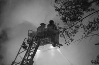 Black & White – firefighters on arial ladder in smoke hose water