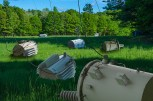 Fantasy – tethered electric transformers graze in field of grass